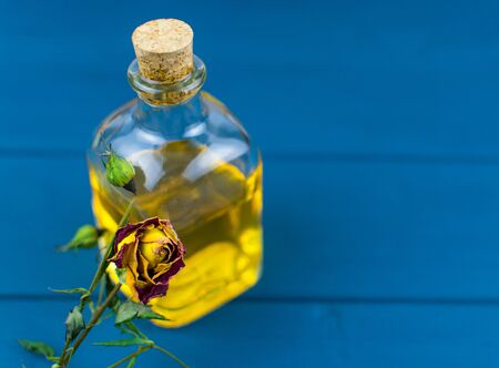 Bottle with elixir on a blue wooden background.