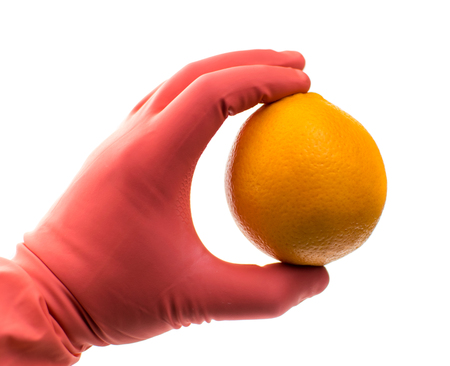 Orange in a hand in a rubber glove on a white background. Isolated. The concept of harmful substances, genetically modified fruits. Stock Photo