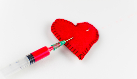 An injection of love in the heart. Stitched heart and syringe with red liquid on a white background.
