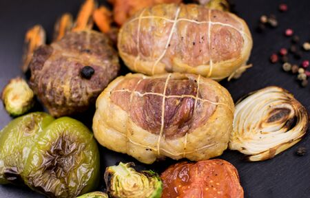Meat products grilled and grilled vegetables on a dark background. Stock Photo