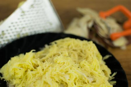 Grated potato on a grater. For cooking dishes from potatoes.