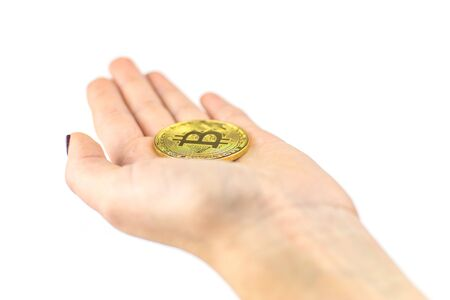 Bitcoin in a female hand on a white background.