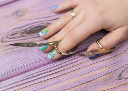 The concept of an unsuccessful manicure. Female hand with manicure and broken scissors. Фото со стока