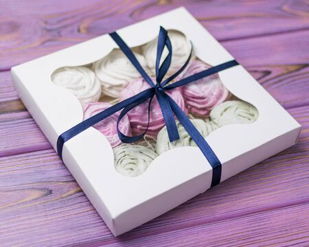 Marshmallow (zephyr) in a gift box on a wooden background. Sweet gift. Stock Photo