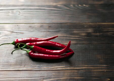 Hot chili peppers on a dark wooden background.