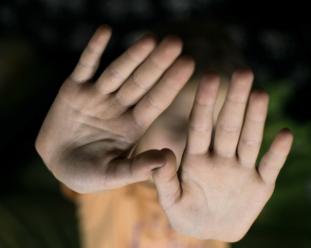 A hand gesture signifying a stop. The girls palm stretched forward. Stock Photo