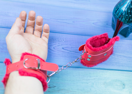 Hand in red handcuff chained to the heel.