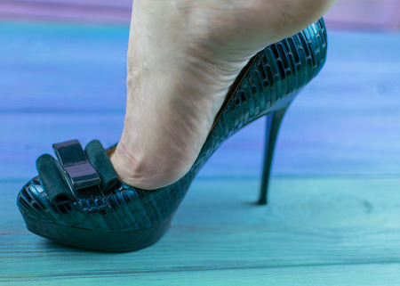 A man's leg in a woman's shoe with a heel. The concept of inappropriate shoe size, orientation disorders.