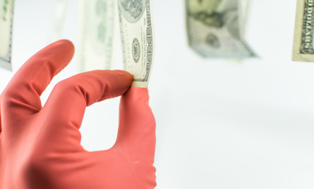 A hand in a rubber glove removes 100 dollars, which hang on the clothespin on a white background.
