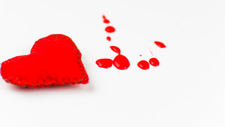 The concept of a bleeding heart. Stitched heart and blood spots on a white background.
