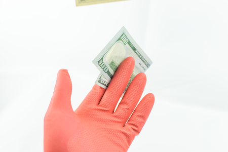 A hand in a rubber glove holds a 100 dollar bill on a white background. The concept of dirty money. Isolated.