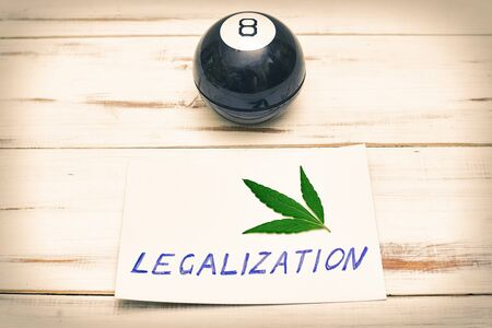 Legalization word with a leaf of marijuana, cannabis and a ball for fortune telling on a light background. Stock Photo