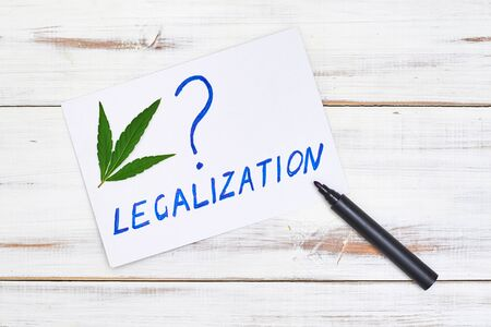 Legalization of marijuana question concept on a light background with cannabis leaf.