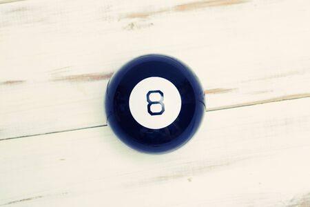 Magic ball of predictions figure eight on a light wooden background.