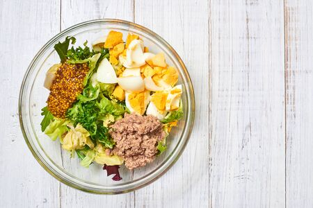 Making a salad of a mix of fresh vegetables and chicken eggs, tuna, mustard, cheese on a white wooden background. Healthy and wholesome organic food, diet, proper nutrition concept.