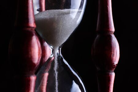 Hourglass close-up on a dark background. Banque d'images