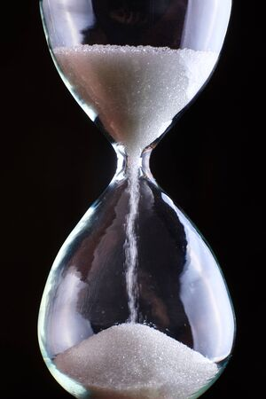 Hourglass close-up on a dark background.