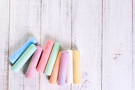 Multicolored chalk for drawing on a light wooden background. The concept of children's creativity.