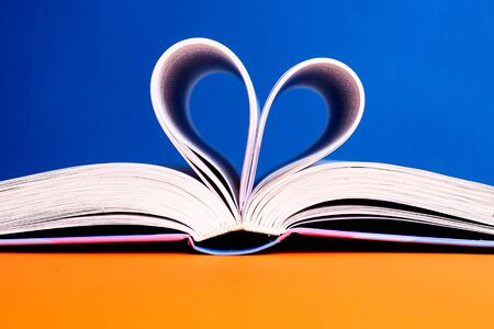 An open book with a folded heart of pages on a blue and yellow background.