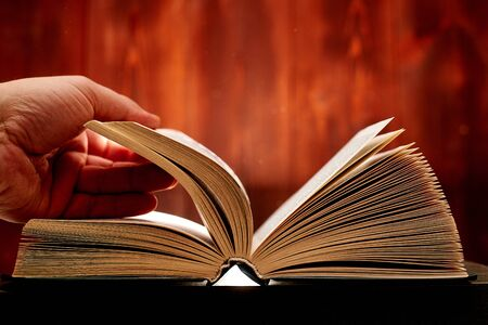 Turn over a thick book. Search for information in a book. Learning concept. Stock Photo
