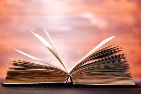 An opened thick book backlit by light on a brown background.