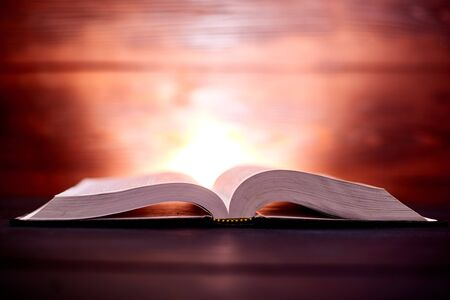 An open book on a shining brown background behind. The concept of learning, reading. Stock Photo