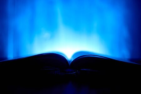 An open book with a glow in the background. Stock Photo