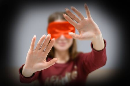The girl comes with a blindfolded eyes blindly to the touch. 版權商用圖片