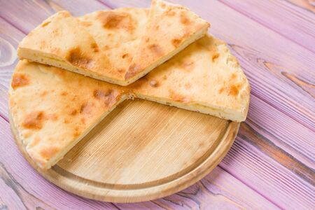 Pie with cheese on a wooden pink background. Khachapuri - flat cake with cheese. Stock Photo