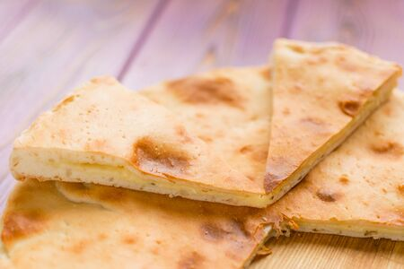 Pie with cheese on a wooden pink background. Khachapuri - flat cake with cheese.