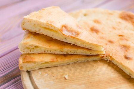Sliced pie with cheese on a wooden background. Khachapuri.