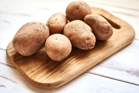 Raw potato tubers on a wooden background.