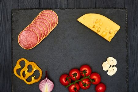 Ingredients for pizza: cheese, sausage, onions, cherry tomatoes, peppers laid out on a black background. Place for text.