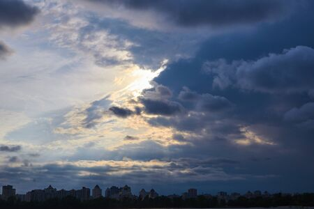 Sun rays breaking through the dark clouds above the river and the city. Foto de archivo