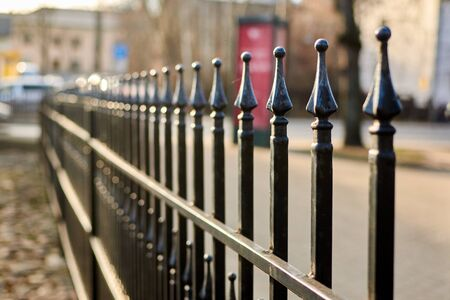 Metal bars of a fence in a row.