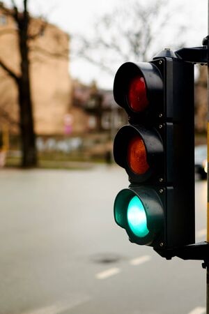 Green traffic light on a city street. A woman is waiting at a pedestrian crossing.