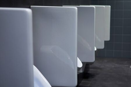 row of urinals in a public restroom.