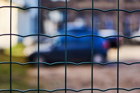 Car behind the fence net. Parking, fine area.
