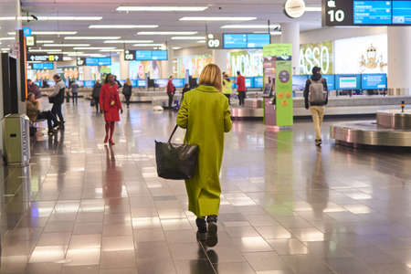 Vienna, Austria - March 10, 2020: A woman in a green coat is walking along the premises of the city's airport.
