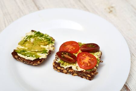 Slice of cereal bread with cream cheese, avocado and vegetables. Vegetarian sandwich.