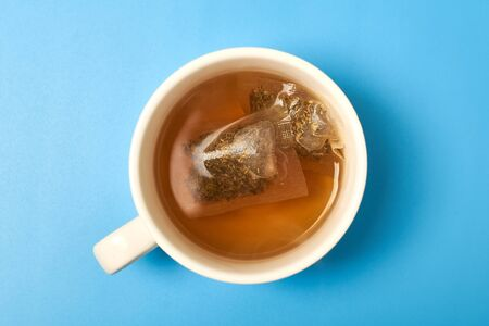 Tea bag in a white cup on a blue background. Making delicious herbal tea.
