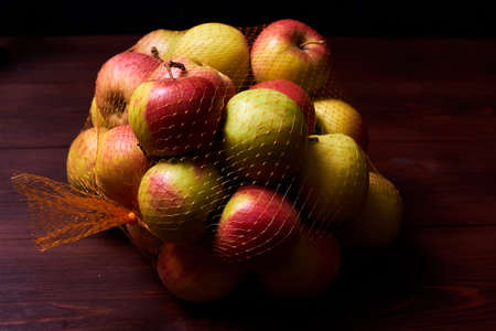 Packing apples in a grid on a wooden background.