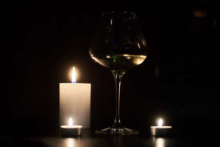 Candles and a glass of wine in the dark.