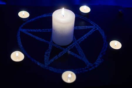 Pentagram and burning candles. The magical ritual of Satanism, invocation of spirits, spiritualistic sessions.