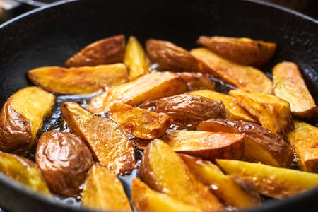 Fried crispy potatoes in oil in a pan. Cooking potatoes in a rustic way.