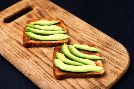 Toast with sliced avocado on a wooden background. Stock Photo