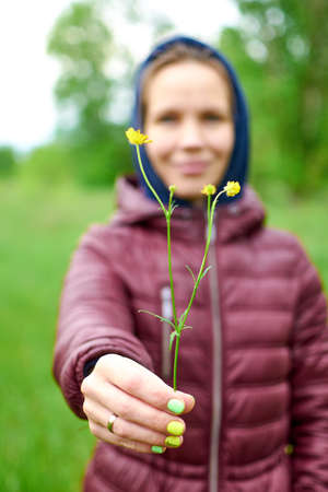 Woman holds wild flower in her hand on a green background. 免版税图像