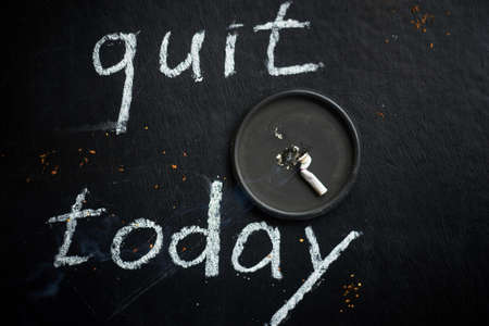 Stop smoking today concept. A quenched cigarette and the inscription -quit today.