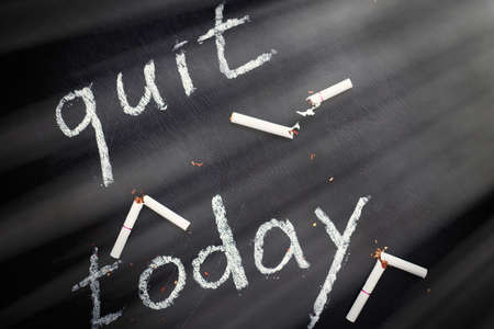 Stop smoking today concept. Broken cigarettes and inscription- quit today.