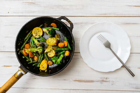Various fried vegetables in a pan. Mix of carrots, green beans, cauliflower.